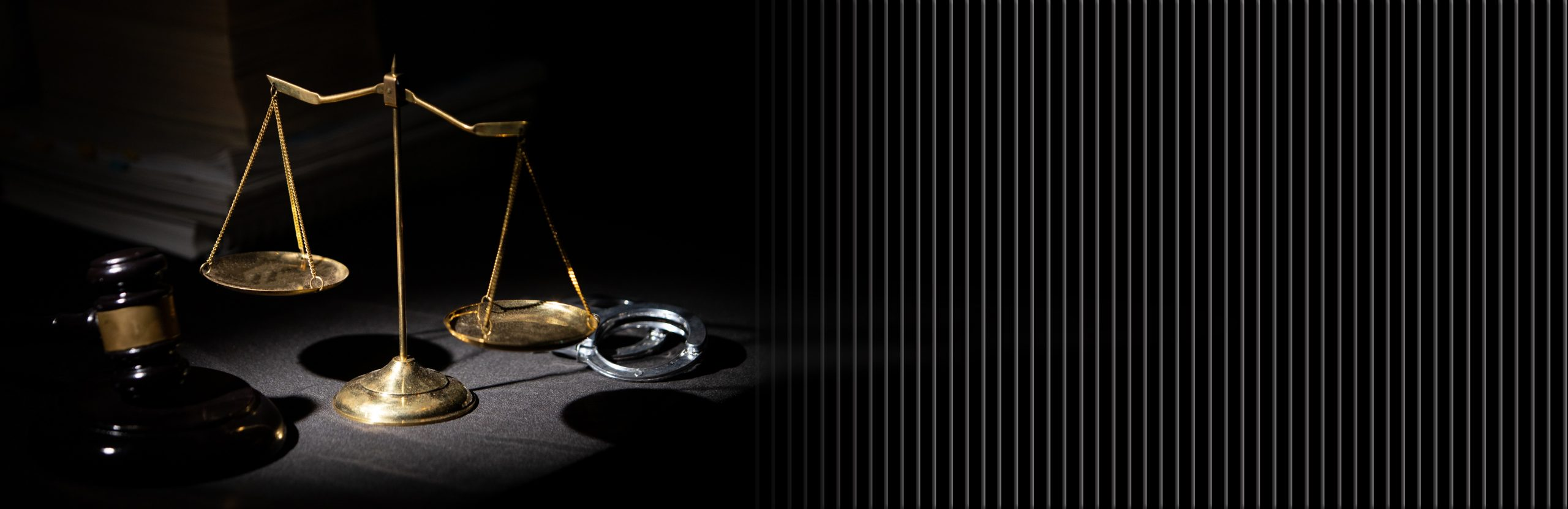 Law Blog - Gavel, Scale, and Cuffs on dark cloth.