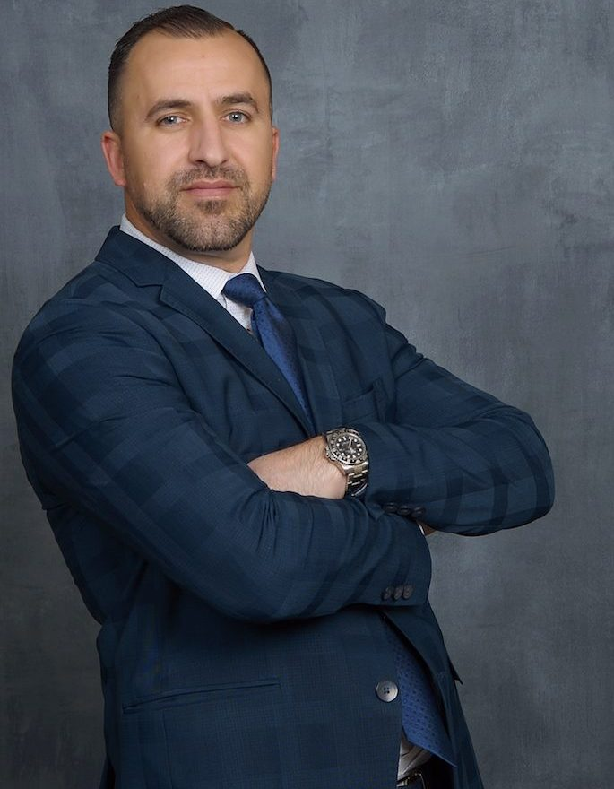 Mesa Criminal Defense Lawyer Brian Soto cross armed in blue square paneled suit