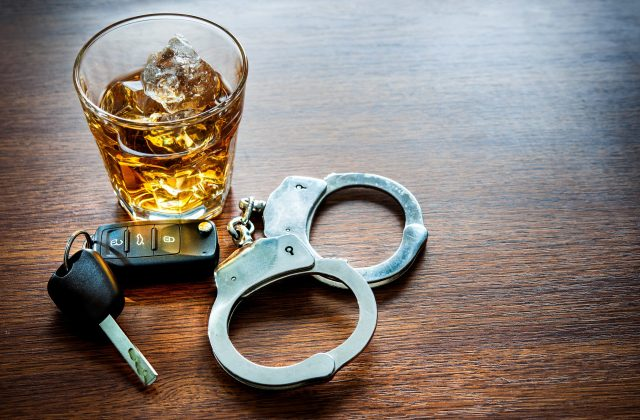 DUI Lawyer - Whiskey glass, keys, and cuffs on wood table